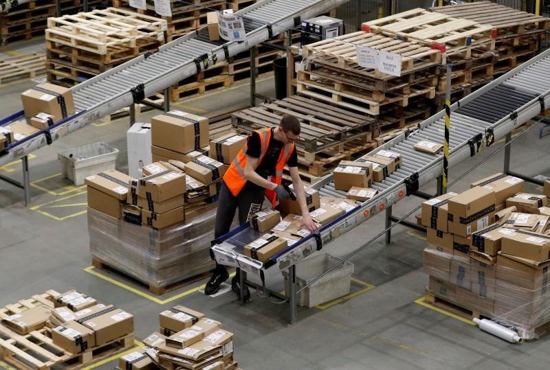 FILE PHOTO: A worker sorts parcels at Amazon's fulfilment centre in Peterborough
