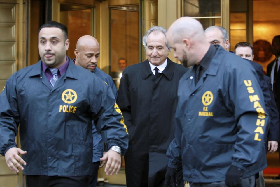 FILE - Disgraced financier Bernard Madoff, center, leaves U.S. District Court in Manhattan escorted by U.S. Marshals after a bail hearing in New York, Monday, Jan. 5, 2009. More than 12 years after Madoff confessed to running the biggest financial fraud in Wall Street history, a team of lawyers is still at work on a sprawling effort to recover money for the thousands of victims of his scam. (AP Photo/Kathy Willens, File)