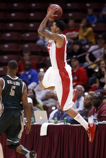 New Mexico's Kendall Williams hits a desperation three pointer over the defense of UAB's Robert Williams to force over time in the second half at the Charleston Classic NCAA college basketball tournament in Charleston, S.C., Thursday, Nov. 21, 2013. (AP Photo/Mic Smith)