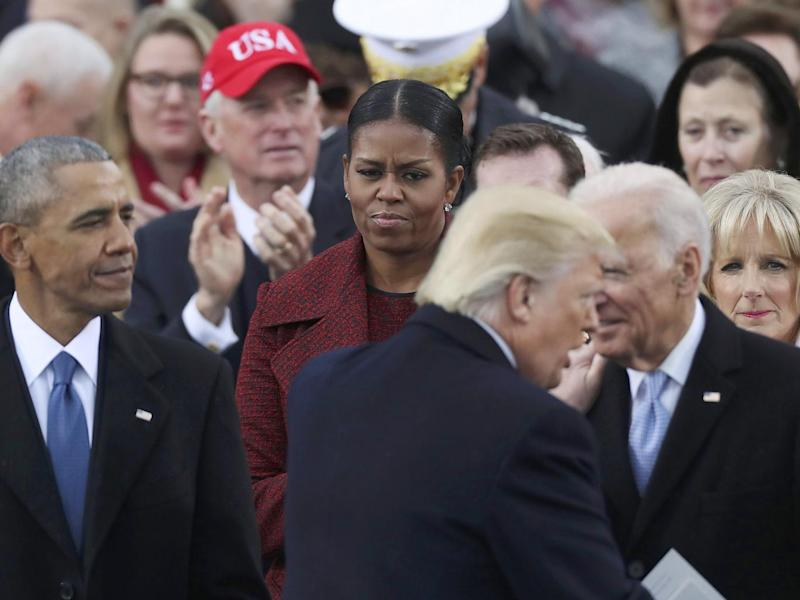 Donald Trump shakes hands with Joe Biden as outgoing President Barack Obama and Michelle Obama look on (Reuters)