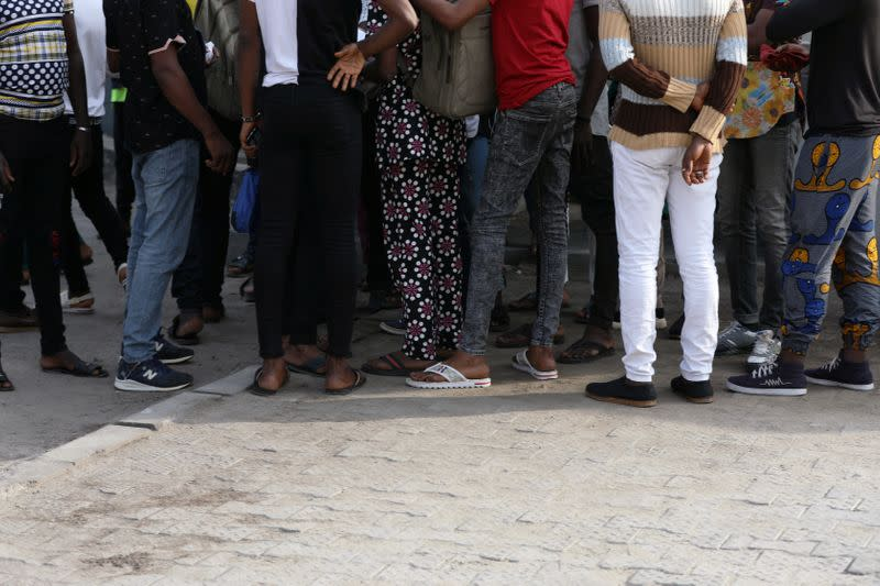 Some of the men charged with public displays of affection with members of the same sex are seen gathered within the premises of the Federal High Court after the court-hearing of their case in Lagos
