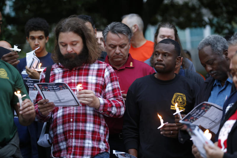 People hold candles during a candlelight vigil outside city hall for deceased and injured workers from the Hard Rock Hotel construction collapse Sat., Oct. 12, in New Orleans, on Thursday, Oct. 17, 2019. The vigil was organized by various area labor groups. (AP Photo/Gerald Herbert)