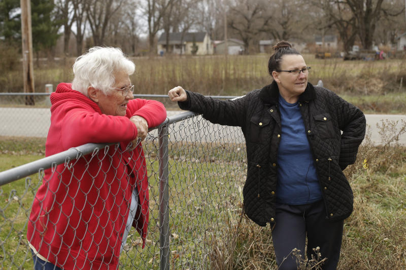 In this photo taken Monday, Nov. 18, 2019, Tammy Kilgore, right, talks to her neighbor Betty Cazzell after Kilgore's home was demolished in Mosby, Mo. Kilgore accepted a $45,000 voluntary buyout offer to leave her flood-prone home of 38 years and has moved to a nearby community. (AP Photo/Charlie Riedel)