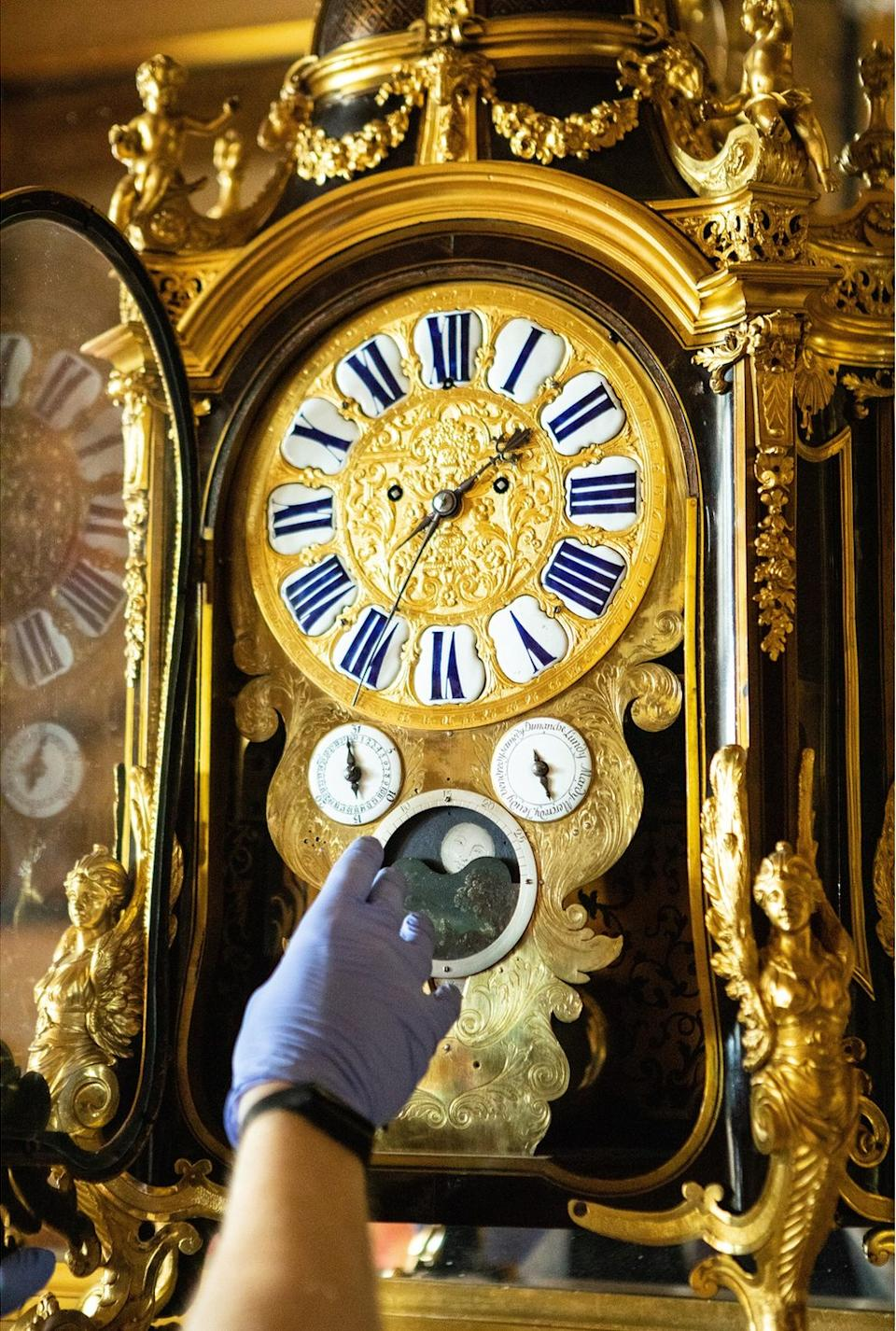 A close-up of Fjodor changing the time on a gold-decorated clock with a dial for moon changes