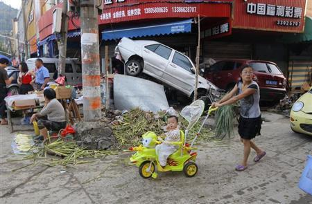 A woman pushes a toy cart carrying a baby next to damaged cars and debris caused by the flood on a street in Yuyao, Zhejiang province October 10, 2013. REUTERS/China Daily/Files