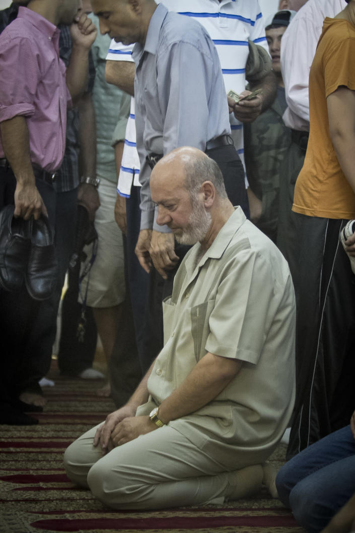 Zein Rimawi, 59, a leader and founder of the Islamic Society of Bay Ridge and mosque, remain kneeling as a Jumu'ah prayer service comes to a close at the a mosque on Friday, Aug. 16, 2013 in the Brooklyn borough of New York. The New York Police Department targeted his mosque as a part of a terrorism enterprise investigation beginning in 2003, spying on it for years. The mosque has never been charged as part of a terrorism conspiracy. (AP Photo/Bebeto Matthews)