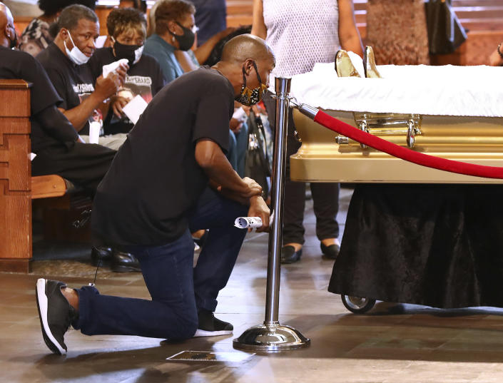 A mourner takes a knee at the coffin during a public viewing for Rayshard Brooks at Ebenezer Baptist Church on Monday, June 22, 2020, in Atlanta. Brooks, 27, who was Black, died June 12 after being shot by a white officer in a Wendy's parking lot. (Curtis Compton/Atlanta Journal-Constitution via AP, Pool)