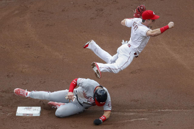 Cincinnati Reds second baseman Scooter Gennett, right, leaps over Washington Nationals' Bryce Harper after forcing him out in the first inning of an opening day baseball game, Friday, March 30, 2018, in Cincinnati. (AP Photo/John Minchillo)