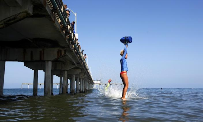 """A San Diego Junior Lifeguard jumps off the Ocean Beach Municipal Pier in August 2018. Coastal cities across California are determining whether to cancel the summer program amid to the coronavirus pandemic. <span class=""""copyright"""">( K.C. Alfred / San Diego Union-Tribune)</span>"""