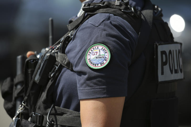 A police officers wearing a G7 badge stands guard while French Interior Minister Christophe Castaner visits the police command room ahead of the upcoming G7 summit, Tuesday, Aug.20, 2019 in Biarritz, southwestern France. French police are setting up checkpoints and combing Atlantic beaches to secure the southwestern coast for world leaders coming for the G-7 summit. (AP Photo/Bob Edme)
