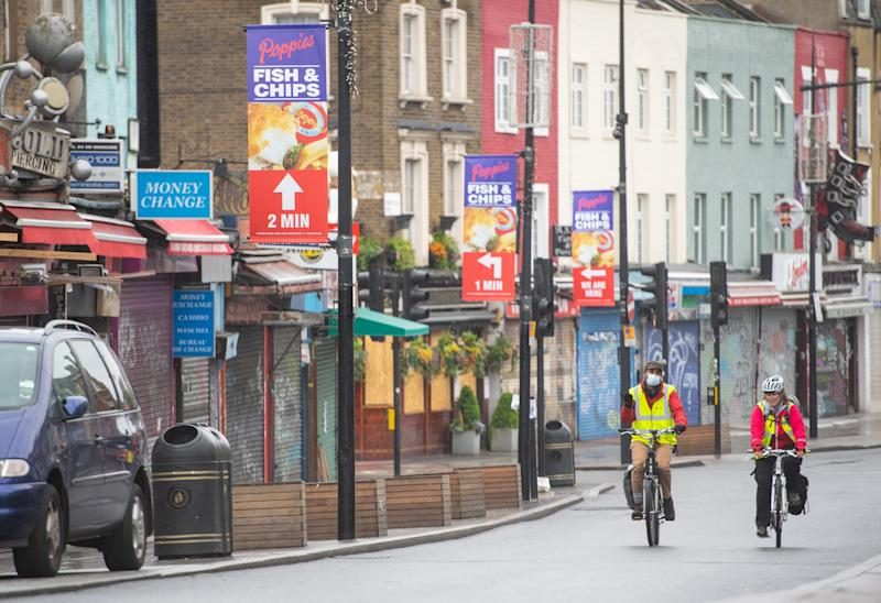 Cyclists ride past shuttered shops on Camden High Street, in north London, as the UK continues in lockdown to help curb the spread of the coronavirus.