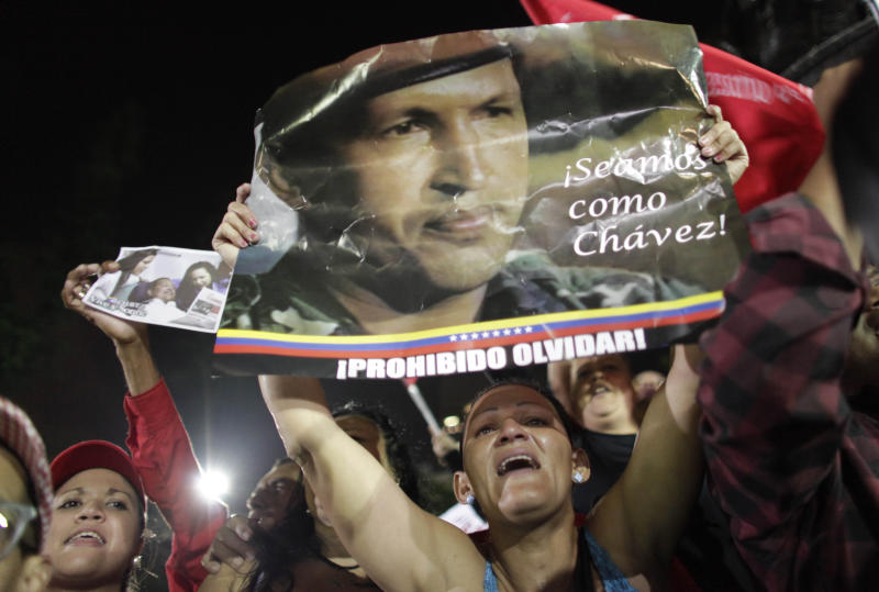 """A supporter of Venezuela's late President Hugo Chavez cries as she holds up a poster of Chavez that reads in Spanish """"Let's be like Chavez"""" and """"Forbidden to forget"""" as Chavistas gather in Bolivar square to mourn Chavez's death in Caracas, Venezuela, Tuesday, March 5, 2013. Venezuela's Vice President Nicolas Maduro announced that Chavez died on Tuesday at age 58 after a nearly two-year bout with cancer. During more than 14 years in office, Chavez routinely challenged the status quo at home and internationally. He polarized Venezuelans with his confrontational and domineering style, yet was also a masterful communicator and strategist who tapped into Venezuelan nationalism to win broad support, particularly among the poor. (AP Photo/Ariana Cubillos)"""