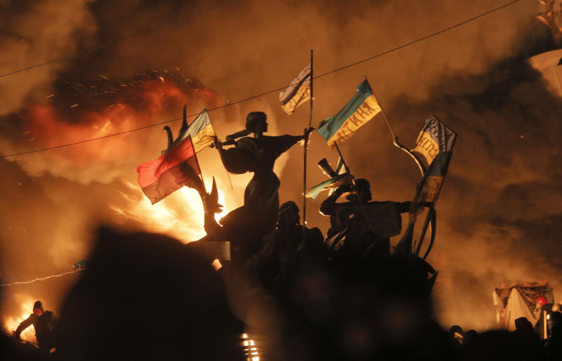 Monuments to Kiev's founders burn as anti-government protesters clash with riot police in Kiev's Independence Square, the epicenter of the country's current unrest, Kiev, Ukraine, Tuesday, Feb. 18, 2014. Thousands of police armed with stun grenades and water cannons attacked the large opposition camp in Ukraine's capital on Tuesday that has been the center of nearly three months of anti-government protests after at least nine people were killed in street clashes. (AP Photo/Efrem Lukatsky)