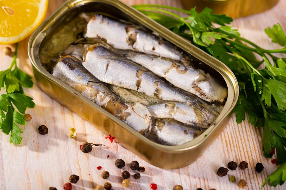 Open can of sardines on table