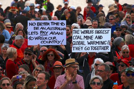 Protesters hold signs as they participate in a national Day of Action against the Indian mining company Adani's planned coal mine project in north-east Australia, at Sydney's Bondi Beach in Australia, October 7, 2017.      REUTERS/David Gray