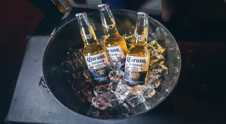 Three bottles of Corona beer are arranged in a bowl with ice.