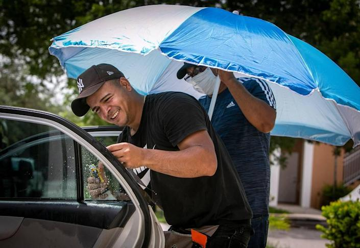 Miami Luxury Window Tinting employee Luis Rivas (left) installs window tinting on his car, and assistant Juan Perez (right) protects both from the scorching sun at Shoma Homes on the corner of Northwest 70th and 177th Avenues. Have a beach umbrella for, Monday, June 21, 2021, Palm Springs North, Miami. Window coloring is usually done in a closed area where workers are protected from the elements, but due to the pandemic, Rivas goes to the customer and involves working outdoors. Exposed to heat and humidity.