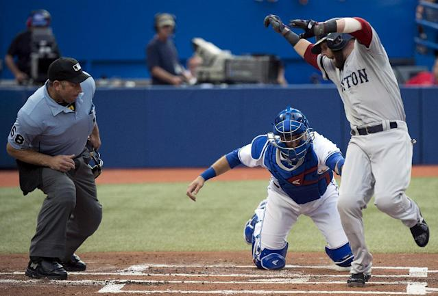 Toronto Blue Jays catcher J.P. Arencibia, center, nearly misses the tag on Boston Red Sox's Dustin Pedroia, right, but finished the out shortly after, as home plate Chris Guccione, left, watches close during first inning of a baseball game on Thursday, Aug. 15, 2013, in Toronto. (AP Photo/The Canadian Press, Nathan Denette)