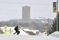 FILE - In this Feb. 7, 2019 file photo, a pair of Bismarck State College students walk across the Bismarck, N.D. campus The state Capitol building is seen in the background. Cities, respectively in North Dakota and Wisconsin, are two of 144 that the federal government is proposing to downgrade from the designation of metropolitan statistical areas, and it could be more than just a matter of semantics. Officials in some of the affected cities worry that raising the bar to 100,000 people could have adverse implications for federal funding and economic development.(Mike McCleary/The Bismarck Tribune via AP, File)