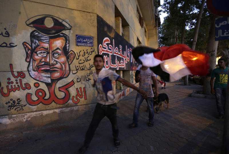 "Graffiti, including a caricature of President Mohammed Morsi, left and ousted President Hosni Munarak, is painted on the wall of a building across from the Ministry of Culture in Cairo, Egypt, Sunday, June 30, 2013. Hundreds of thousands of opponents of Egypt's Islamist president poured out onto the streets in Cairo and across much of the nation Sunday, launching an all-out push to force Mohammed Morsi from office on the one-year anniversary of his inauguration. Fears of violence were high, with Morsi's Islamist supporters vowing to defend him. The red Arabic words below the face drawing reads, ""Whoever cost it didn't die."" The Arabic next to the face drawing reads, ""Down with the rule of sheep."" The red and white Arabic reads, ""The revolution is everywhere against the killer and the traitor."" (AP Photo/Hiro Komae)"