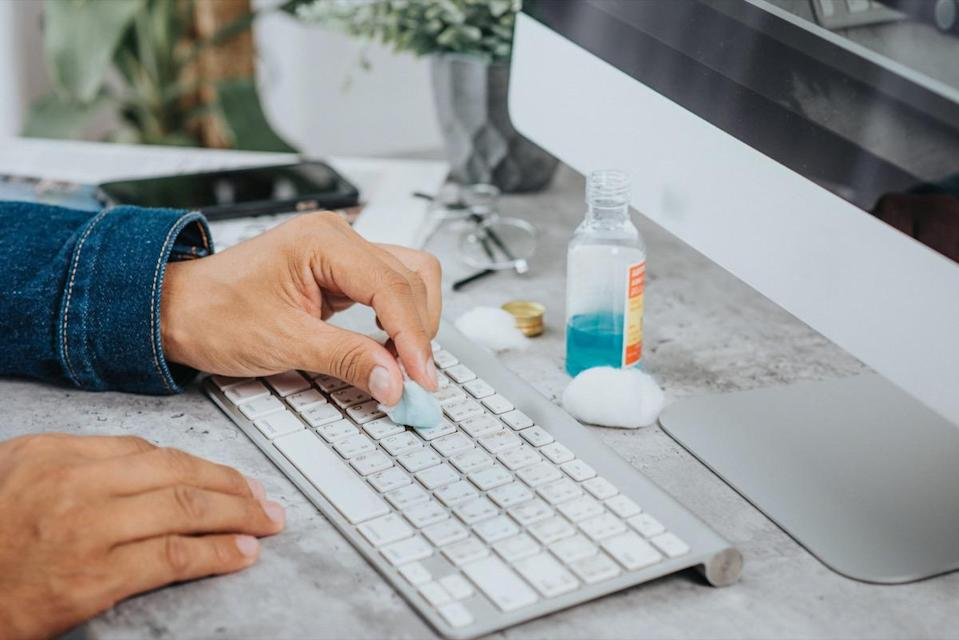 man cleaning his computer keyboard