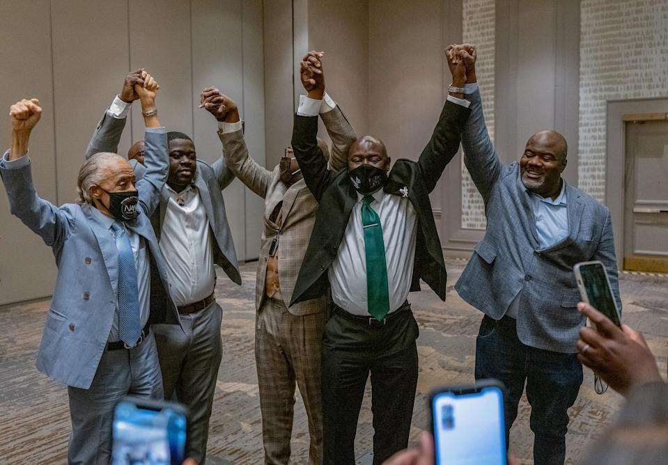 """Attorney Ben Crump (C), with Reverend Al Sharpton (L) and members of George Floyd's family, reacts following the guilty verdict in the trial of former police officer Derek Chauvin in Minneapolis on April 20.<span class=""""copyright"""">Ruddy Roye for TIME</span>"""