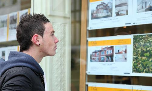 A young man views listing in an estate agent's window