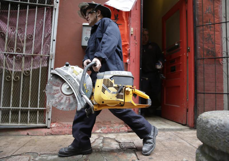 A San Francisco fireman carries away a saw after assisting FBI agents during a search of a Chinatown fraternal organization Wednesday, March 26, 2014, in San Francisco. A California state senator was arrested Wednesday during a series of raids by the FBI in Sacramento and the San Francisco Bay Area, authorities said. An FBI spokesman confirmed the arrest of State Sen. Leland Yee, but declined to discuss the charges, citing an ongoing investigation. (AP Photo/Eric Risberg)