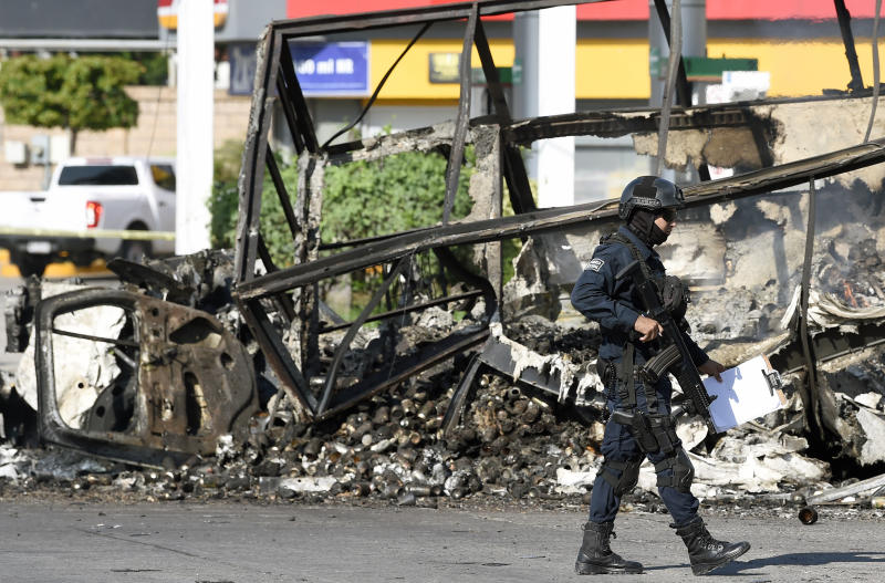 """A policeman walks past a burnt vehicle after heavily armed gunmen waged an all-out battle against Mexican security forces in Culiacan, Sinaloa state, Mexico, on October 18, 2019. - Mexico's president faced a firestorm of criticism Friday as his security forces confirmed they arrested kingpin Joaquin """"El Chapo"""" Guzman's son, then released him when his cartel responded with an all-out gun battle. (Photo by ALFREDO ESTRELLA / AFP) (Photo by ALFREDO ESTRELLA/AFP via Getty Images)"""
