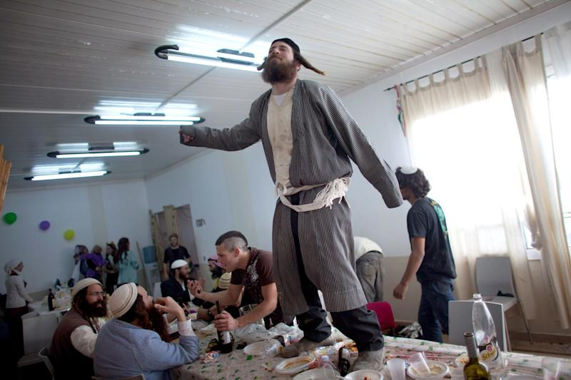 A Jewish settler wears a costume and dances on a table as they celebrate the Jewish festival of Purim February 24, 2013 at the settlement outpost of Havat Gilad, West Bank. (Photo by Uriel Sinai/Getty Images)Ê