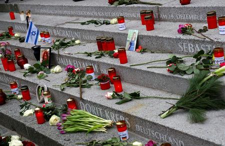 FILE PHOTO: Flowers and candles are placed to commemorate the victims of the 2016 Christmas market truck attack at Breitscheidplatz square in Berlin, Germany, December 19, 2018. REUTERS/Fabrizio Bensch/File Photo