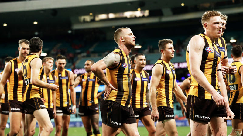 Hawthorn players walking off looking dejected.