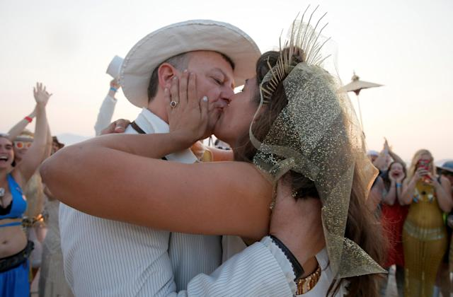 <p>Burning Man participant Dustin Smith kisses his wife Rebecca Wyatt as they are married in the middle of the desert during the 4th day of the annual Burning Man arts and music festival in the Black Rock Desert of Nevada, Aug. 31, 2017. (Photo: Jim Bourg/Reuters) </p>