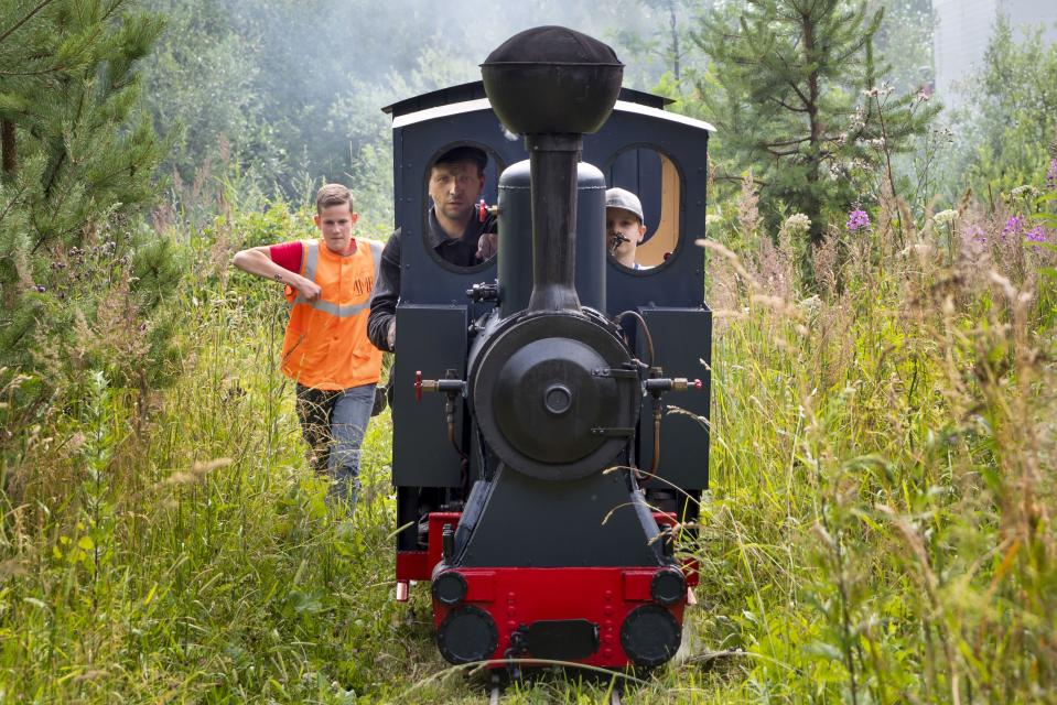 A steam train travels at a private railway near Pavel Chilin's cottage home in Ulyanovka village, about 50 kilometers (31 miles) south of St.Petersburg, Russia Sunday, July 19, 2020. It took Chilin more than 10 years to build the 350-meter-long miniature personal narrow-gauge railway complete with various branches, dead ends, circuit loops, and even three bridges. (AP Photo/Dmitri Lovetsky)