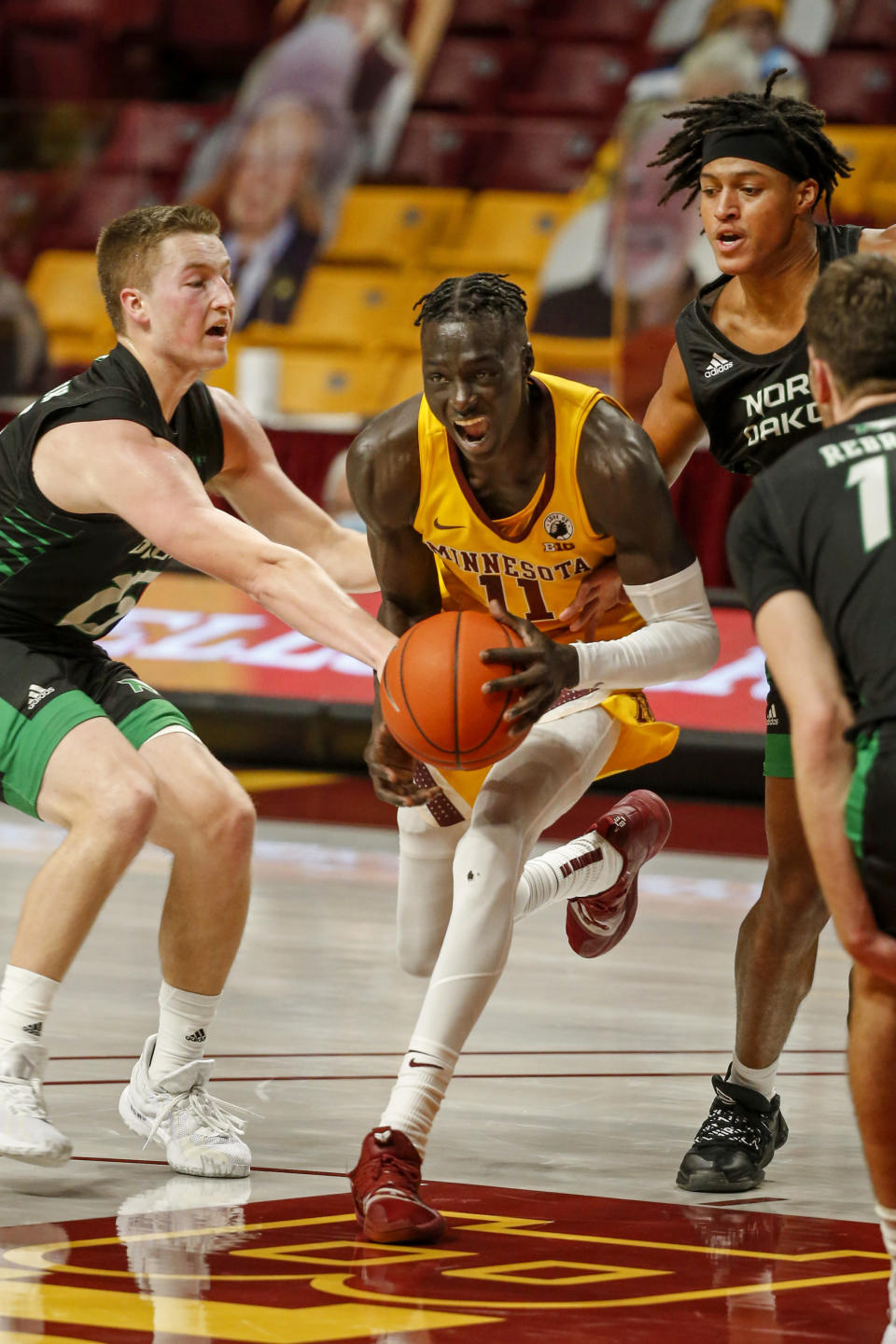 Minnesota guard Both Gach (11) works between the defense of North Dakota forward Brady Danielson (15) and guard Tyree Ihenacho (4) in the first half of an NCAA college basketball game Friday, Dec. 4, 2020, in Minneapolis. (AP Photo/Bruce Kluckhohn)