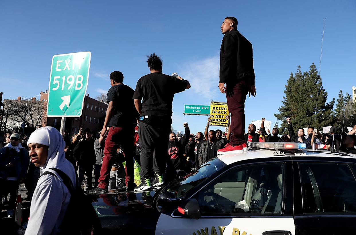 Protesters stand on a California Highway Patrol car on Interstate 5.