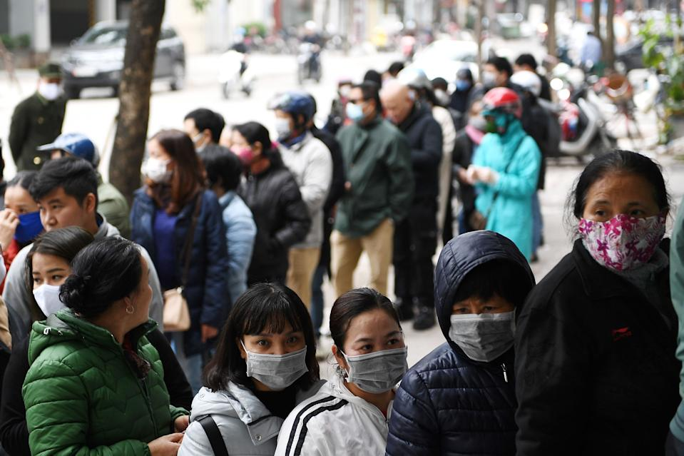 People line up to buy protective face masks amid concerns of the novel coronavirus outbreak that originated in central China, outside a shop in Hanoi on February 10, 2020. - Vietnam repatriated 30 citizens February 10 from Wuhan, where the SARS-like novel coronavirus originated. (Photo by Nhac NGUYEN / AFP) (Photo by NHAC NGUYEN/AFP via Getty Images)