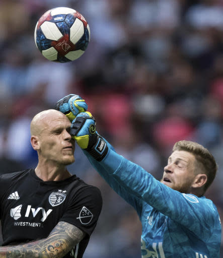 Vancouver Whitecaps goalkeeper Zac MacMath, right, punches the ball away as Sporting Kansas City's Botond Barath attempts to get his head on it off a corner kick during the first half of an MLS soccer game in Vancouver, British Columbia, Saturday, July 13, 2019. (Darryl Dyck/The Canadian Press via AP)