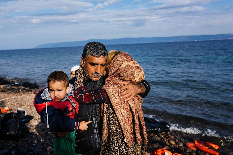 A family pictured shortly after arriving with other migrants and refugees on the Greek island of Lesbos on October 12, 2015, after crossing the Aegean Sea from Turkey (AFP Photo/Dimitar Dilkoff)