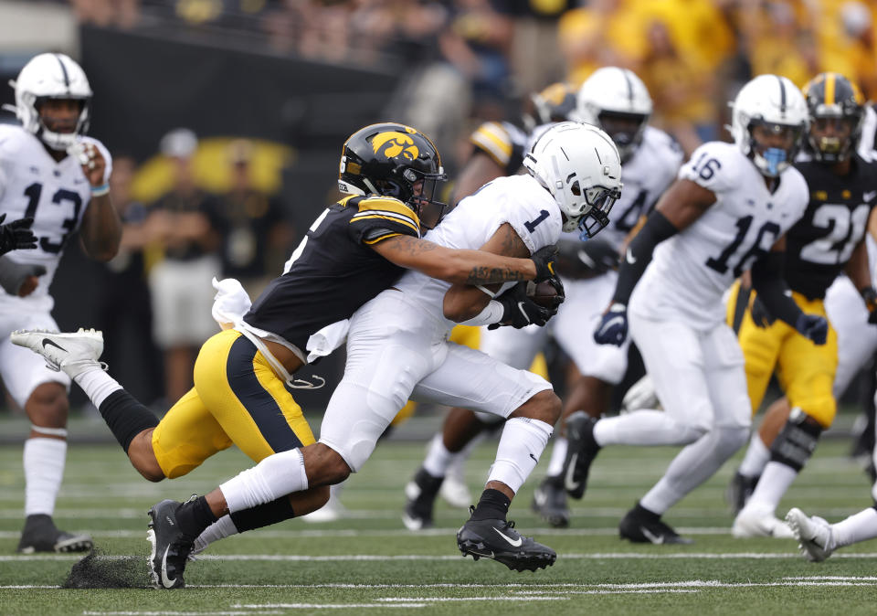 Penn State safety Jaquan Brisker (1) runs back an interception as Iowa wide receiver Keagan Johnson (6) makes the tackle during the first half of an NCAA college football game, Saturday, Oct. 9, 2021, in Iowa City, Iowa. (AP Photo/Matthew Putney)