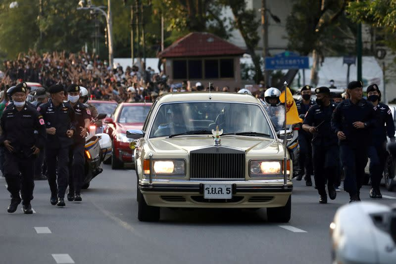 The royal motorcade carrying Thailand's Queen Suthida and Prince Dipangkorn drives past a group of anti-government demonstrators in front of Government House in Bangkok