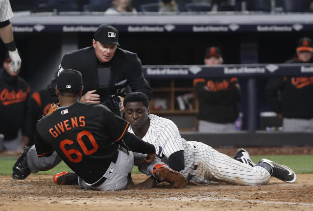 New York Yankees' Didi Gregorius (18) is tagged out at home plate by Baltimore Orioles pitcher Mychal Givens as he tried to score on a wild pitch during the 11th inning of a baseball game Friday, April 6, 2018, in New York. (AP Photo/Julie Jacobson)