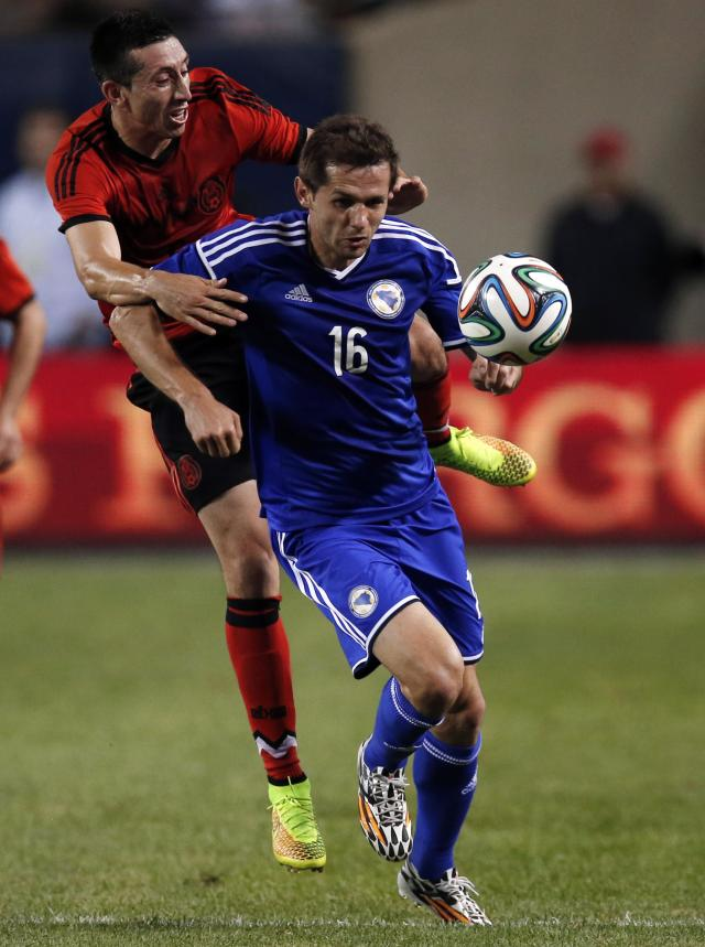 Mexico's Hector Herrera battles for the ball against Bosnia and Herzegovina's Senad Lulic during their international friendly soccer match at Soldier Field in Chicago