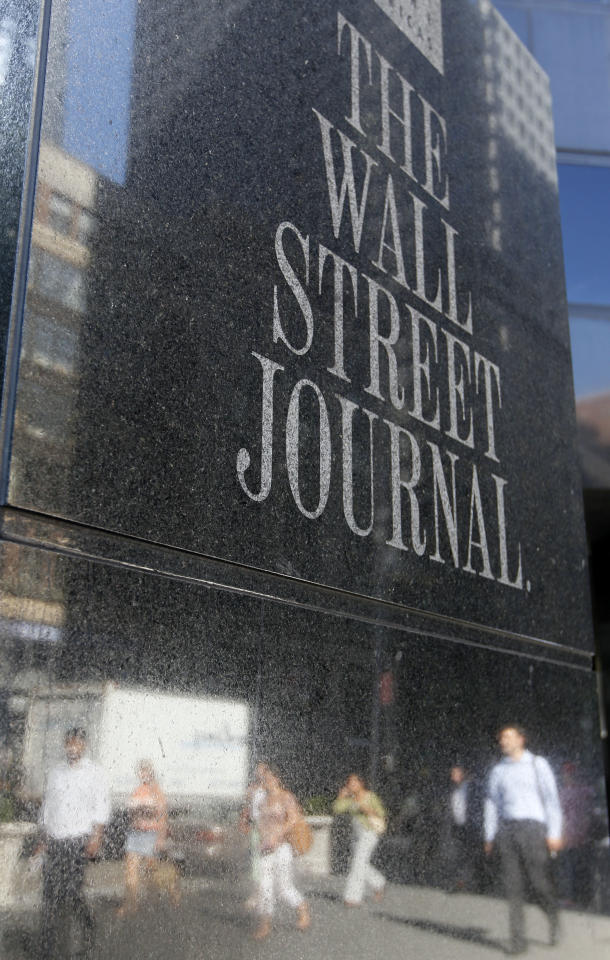 People are seen reflected in a Wall Street Journal sign outside a building, Friday, July 15, 2011, in New York. Rupert Murdoch accepted the resignation of The Wall Street Journal's publisher and the chief of his British operations on Friday as the once-defiant media mogul struggled to control an escalating phone hacking scandal with apologies to the public and the family of a murdered schoolgirl. The controversy claimed its first victim in the United States as Les Hinton, chief executive of the Murdoch-owned Dow Jones & Co. and publisher of the Wall Street Journal, announced he was resigning, effective immediately. (AP Photo/Mary Altaffer)
