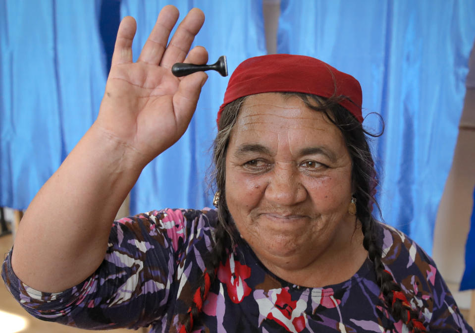 A woman holds up the voting stamp she used, at a polling station in Sintesti, Romania, Sunday, Nov. 10, 2019. Romania held a presidential election Sunday after a lackluster campaign that has been overshadowed by the country's political crisis, which saw a minority government installed just a few days ago. (AP Photo/Vadim Ghirda)