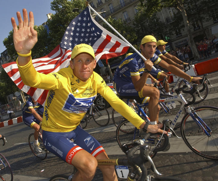 FILE - In this July 25, 2004 file photo, U.S. Postal Service cycling team leader and 2004 Tour de France winner Lance Armstrong, wearing the overall leader's yellow jersey, and teammate George Hincapie, right, ride the victory lap on Champs Elysees boulevard in Paris, France. Lawyers for Armstrong say the Justice Department has joined a lawsuit against the cyclist. The lawsuit alleges the former Tour de France champion concealed his use of performance-enhancing drugs for over a decade and defrauded his long-time sponsor, the U.S. Postal Service. (AP Photo/Peter Dejong, File)