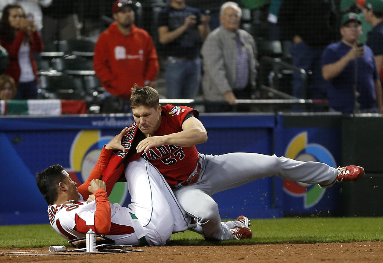 Canada's Jay Johnson, right, and Mexico's Eduardo Arredondo fight during the ninth inning of a World Baseball Classic game, Saturday, March 9, 2013, in Phoenix. (AP Photo/Matt York)
