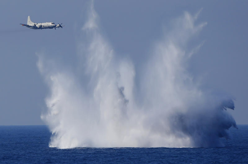 FILE - In this Oct. 18, 2015, file photo, a P-3C anti-submarine patrol plane of the Japan Maritime Self-Defense Force (JMSDF) flies after dropping anti-submarine bombs during the official triennial JMSDF fleet review in the waters off Sagami Bay, south of Tokyo. Japan on Friday, Dec. 27, 2019, approved a contentious plan to send its naval troops to the Middle East to contribute to the peace and stability in the area and ensure the safety of Japanese ships transporting oil, a mission crucial to an energy-poor country that heavily depends on oil imports from the region. (AP Photo/Shizuo Kambayashi, File)