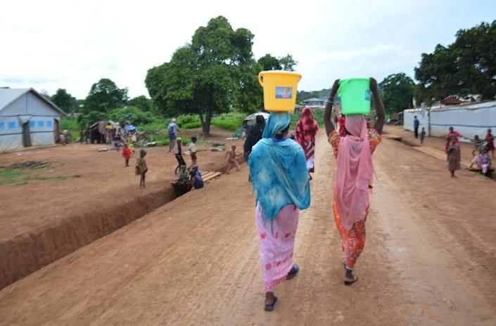 Women carry buckets of water in the streets of the Muslim area in Boda, southern Central African Republic on May 21, 2015 (AFP Photo/Patrick Fort)