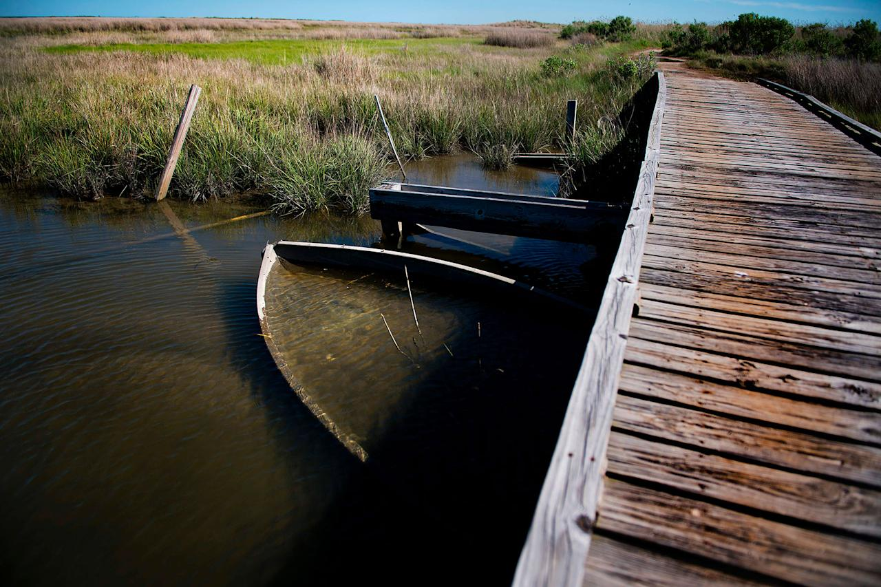 <p>A submerged boats rests under a bridge in Tangier, Virginia, May 15, 2017, where climate change and rising sea levels threaten the inhabitants of the slowly sinking island.<br /> (Jim Watson/AFP/Getty Images) </p>